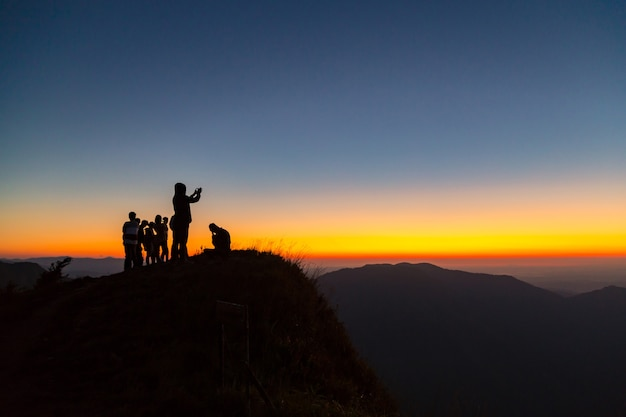 Silhouettes of people on mountains