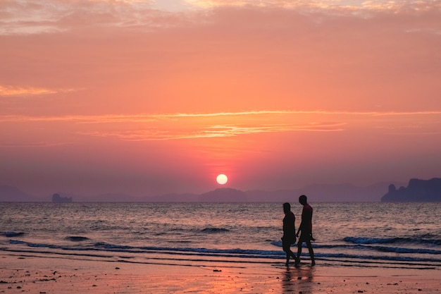 Silhouettes of people on a of a sunset sea landscape