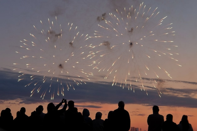 Silhouettes of people watching fireworks at sunset