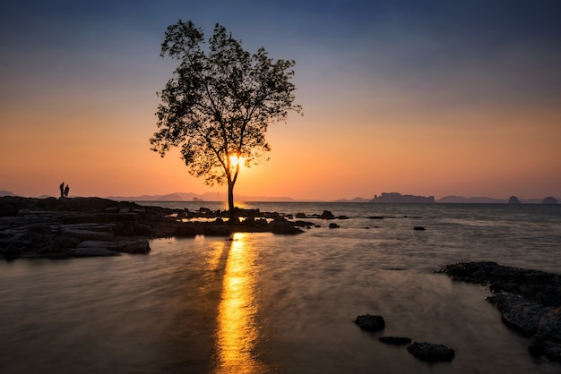 Silhouettes of people watching seascape at sunset of koh kwang island h in krabi, thailand