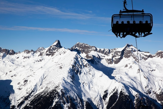 Silhouettes of people with skis and snowboards on a chairlift against a mountain panorama on a clear sunny day. ischgl austria