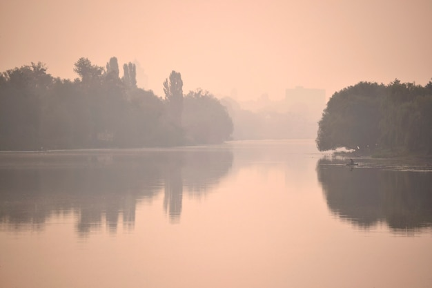 Silhouettes of river banks in a pink fog mist at sunrise sunset