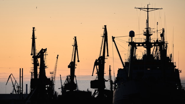 Silhouettes of ships and container cranes in sea port, sunset  sky