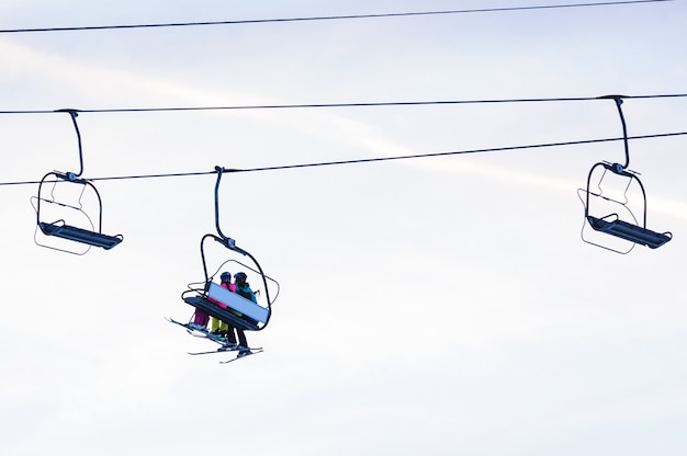 Silhouettes of skiers on chair lifts in the evening