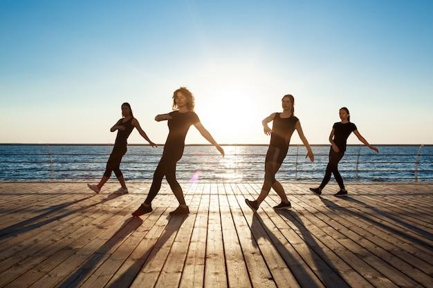 Silhouettes of sportive women dancing zumba near sea at sunrise