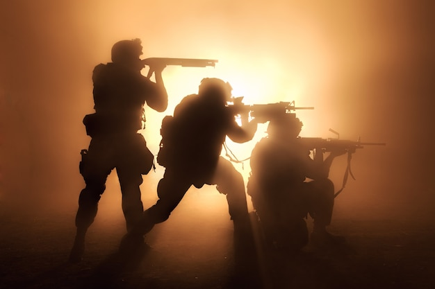 Silhouettes of three army soldiers us marines team in action surrounded fire and smoke shooting