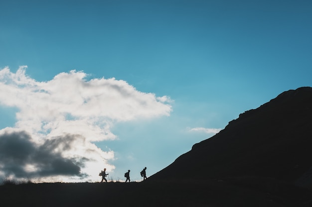 Silhouettes of travelers-tourists climbing uphill against the background of clouds and blue sky
