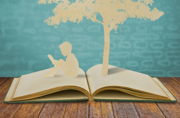 Silhouettes of a tree and a man on a book