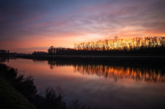 Silhouettes of trees under the cloudy sunset sky reflected in the lake below
