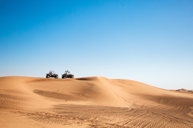 Silhouettes of two buggy quad bikes up on sand hill with sky at dubai desert