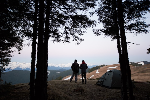 Silhouettes of two men standing near their tent on top of the mountain while out camping together