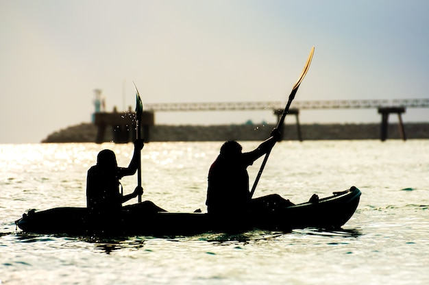 Silhouettes two people rowing on a sea
