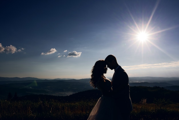 Silhouettes of wedding couple standing in the rays of sun before mountain landscape