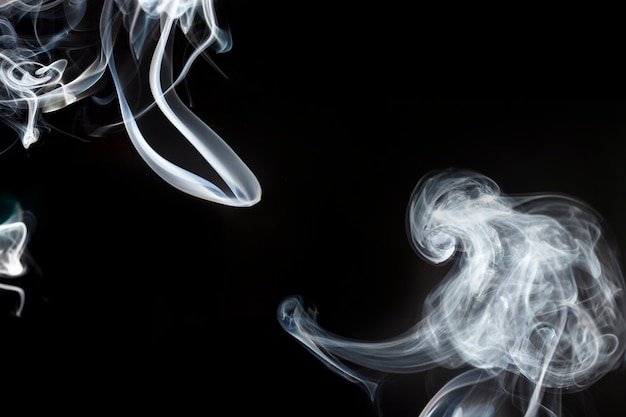 Silhouettes of white smoke in motion