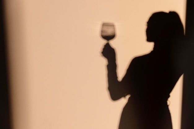 Silhouettes of woman drinking wine