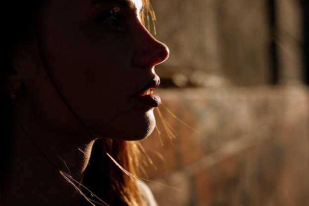 街のクローズアップで太陽の下で女性のシルエット。女性の唇