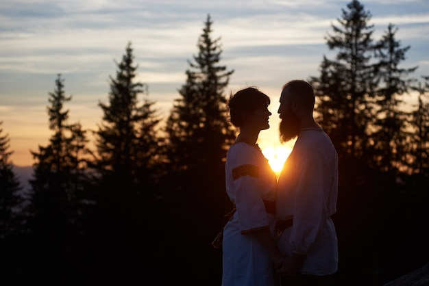 Silhouettes of young couple in love at sunset