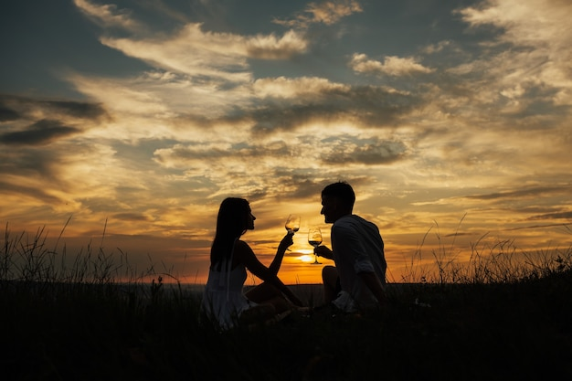 Silhouettes of young man and woman on holidays or honeymoon at amazing sunset sky.
