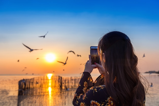 Silhoutte of birds flying and young woman taking a photo at sunset.