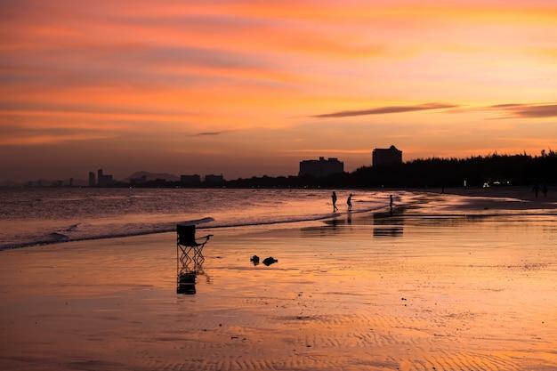 황혼의 하늘, 차암과 함께 황혼에 행복한 가족 배경이 있는 silhoutte 의자와 샌들 ob 해변