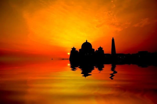 물 반사가 있는 모스크 위로 일몰의 실루엣 이미지