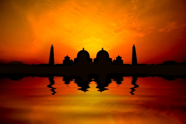 Silhoutte image of sunset over a mosque with water reflection