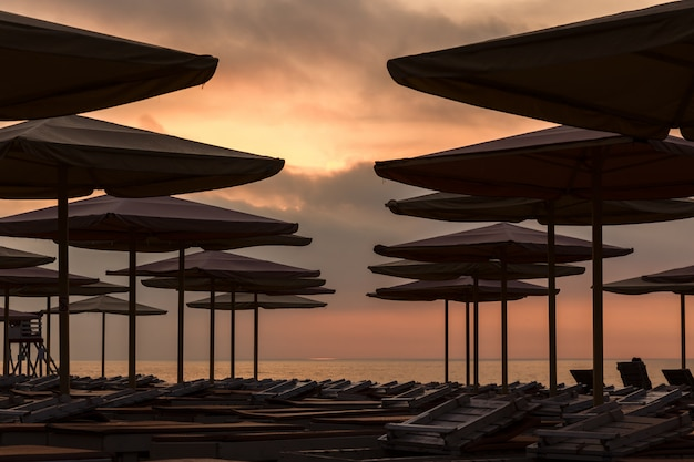 Silhuettes of beach loungers and umbrellas on an empty beach in the evening on a sunset background