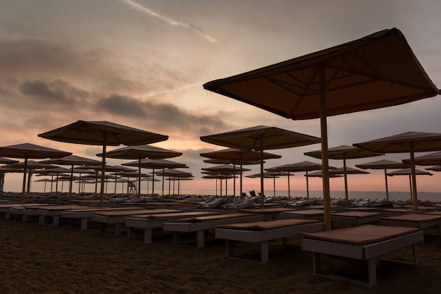 Silhuettes of beach loungers and umbrellas on an empty beach in the evening