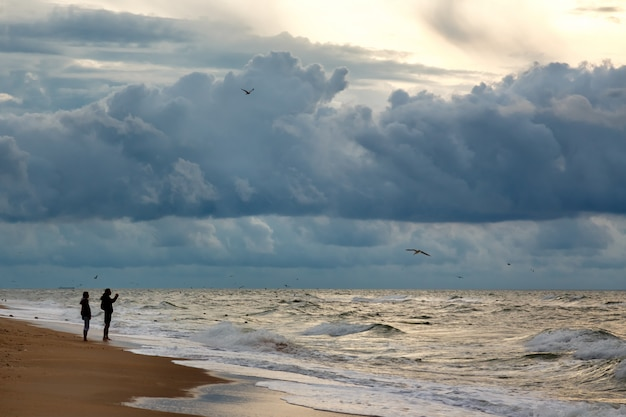 Silhuettes of two people makinf photo of dramatic sky on a morning seascape.