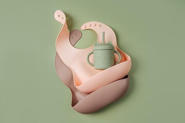 녹색 배경에 실리콘 아기 턱받이입니다. 저녁 식사를 위한 첫 번째 아기 액세서리. 평면도, 평면도