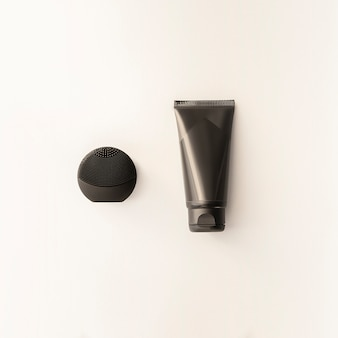 Silicone black face brush and cream black tube isolated. mockup for male accessories.beauty blog concept.men cosmetics flat lay for branding. set of black personal hygiene products