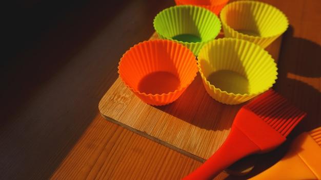 木製のテーブルにシリコンブラシとカップケーキライナー。木製の背景にキッチンと料理のコンセプト