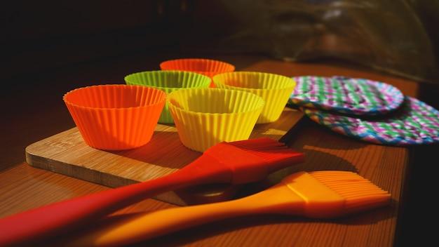 나무 테이블에 실리콘 브러시와 컵케이크 라이너. 나무 배경에 부엌과 요리 개념