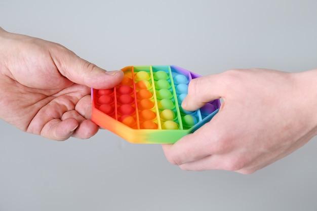 실리콘 다채로운 안티 스트레스 팝 손에 육각형 모양의 장난감. 확대.