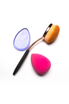 Silicone foundation sponge, oval brush and beauty blender isolated on a white background