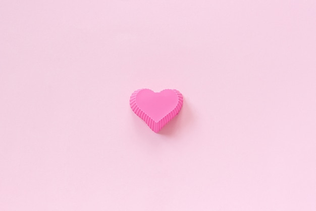 Silicone heart shaped mold dish for baking cupcakes on pink paper background.