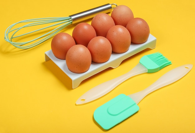 Silicone kitchen tools (spatula, brush and whisk), tray of eggs on yellow.