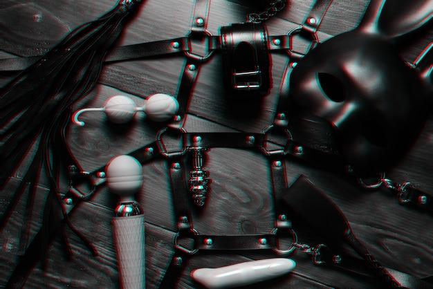 シリコンバイブレーターと膣ボール、革の鞭とマスクとベルト付きの手錠。緊縛とオナニーのための女性のセックスエロアクセサリー