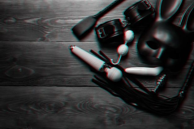 Силиконовый вибратор и вагинальные шарики, кожаный хлыст и наручники с маской и поясом