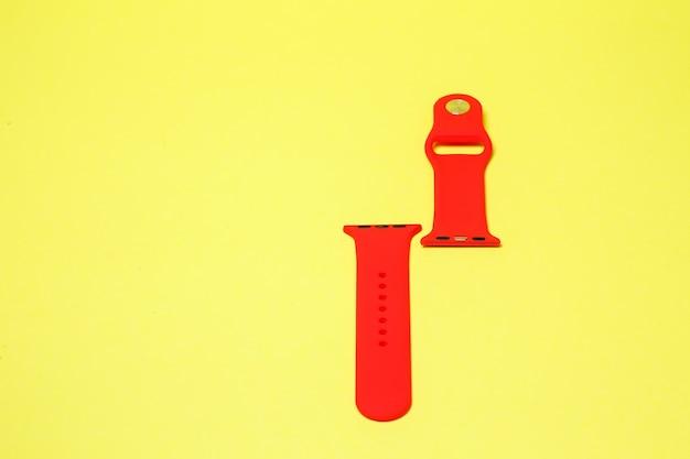 黄色の背景にスマートウォッチの赤い色のシリコンストラップ