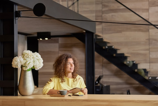 Siling curly girl looking at side, keeping blocknote sitting on wooden table.