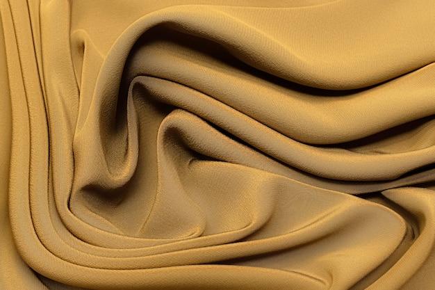 Ткань шелковый шифон песочного и коричневого цвета в художественной раскладке. текстура, фон, узор.