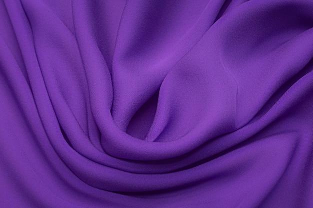 Шелковая ткань крепдешин сиреневого цвета в художественной выкладке. текстура, фон. шаблон.