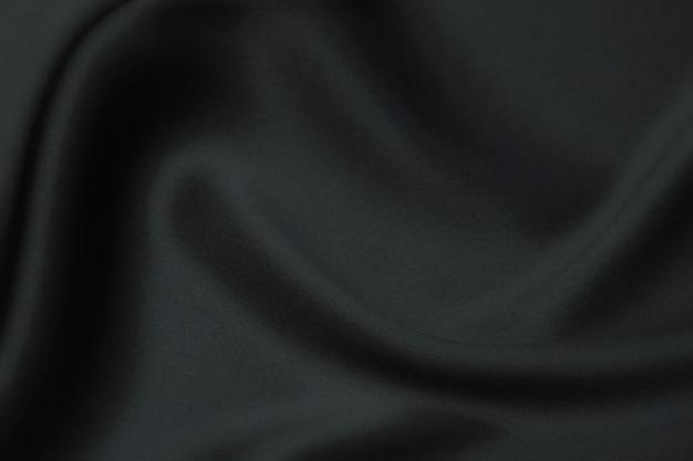 シルクまたはコットン生地のティッシュ。ダークグレーまたはブラックカラー。テクスチャ、背景、パターン。