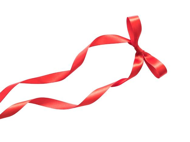 白い背景で隔離の絹の赤いリボンの弓