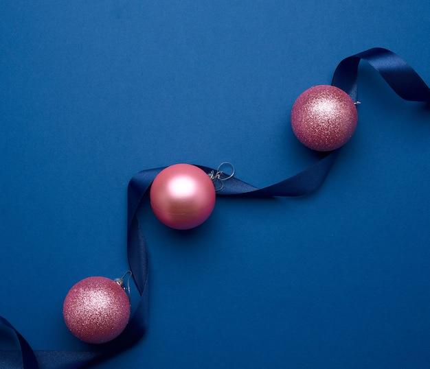 실크 리본과 파란색 배경에 분홍색 반짝이 크리스마스 공, 축제 배경