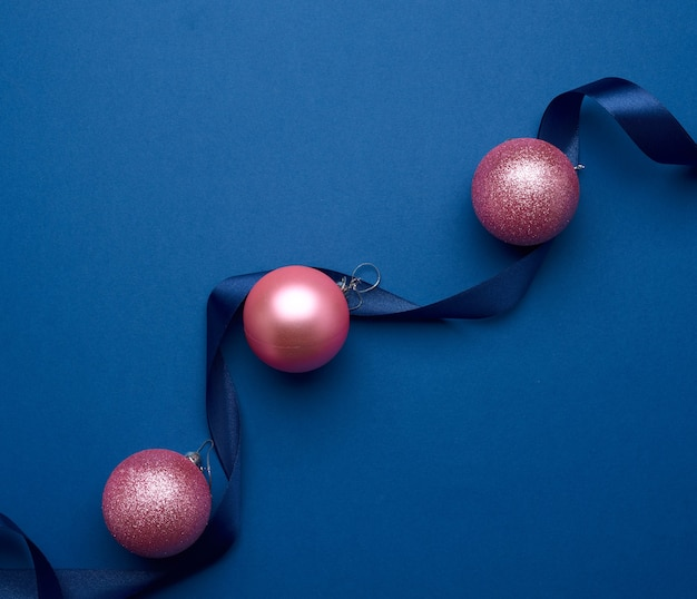 Silk ribbon and pink shiny christmas balls on a blue background, festive backdrop