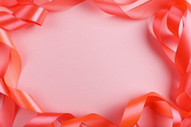 실크 리본은 밝은 분홍색 배경에 프레임 상위 뷰를 비 웁니다.