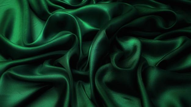 Шелковая атласная ткань. зеленый цвет. текстура, фон, узор.