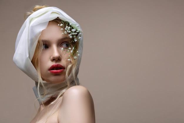 絹のスカーフ。彼女の頭に白い絹のスカーフと壁の近くでポーズをとっている開いた肩を持つ青い目のモデル